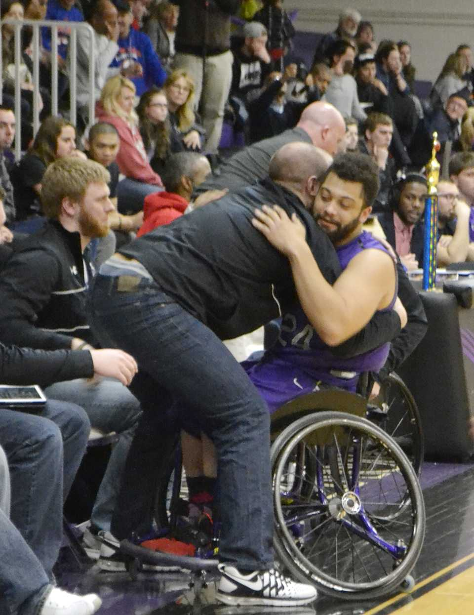 Senior Jordan Scheidecker hugs an assistant on the bench as he is subbed out for a final time as a Warhawk. Scheidecker is one of three 'Hawks graduating. Photo by Sierra High