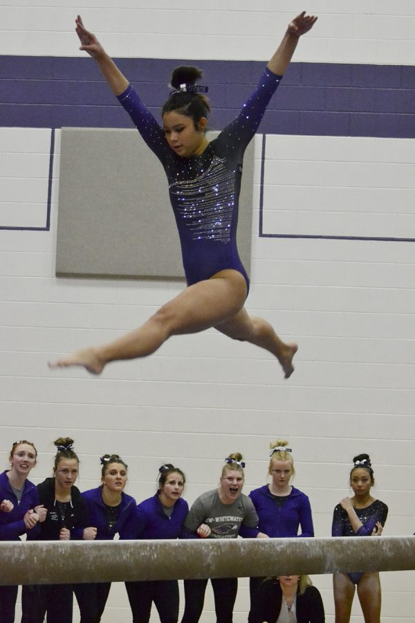 Sophomore+Franchesca+Hutton+leaps+in+the+air+during+her+%0Abalance+beam+routine+as+her+teammates+cheer+her+on+in+the+March+11+victory+against+Hamline+University.+Photo+by+Sierra+High