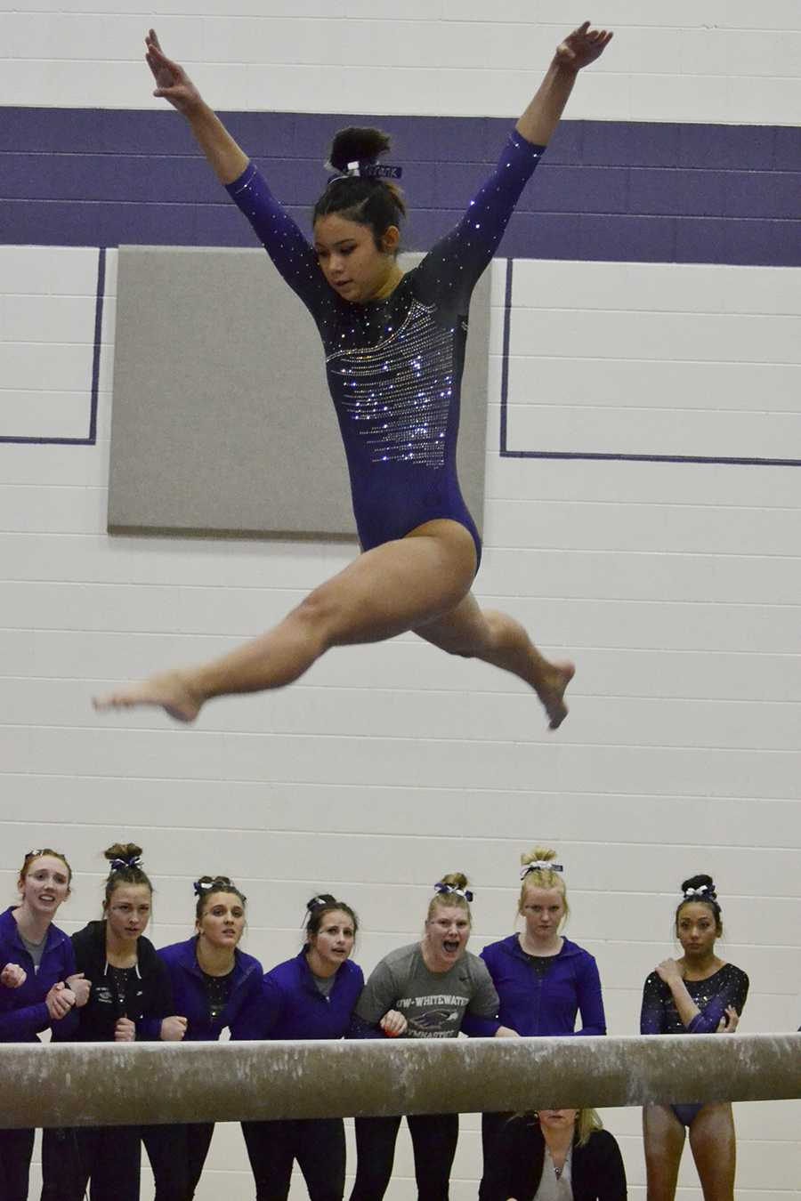 Sophomore Franchesca Hutton leaps in the air during her  balance beam routine as her teammates cheer her on in the March 11 victory against Hamline University. Photo by Sierra High