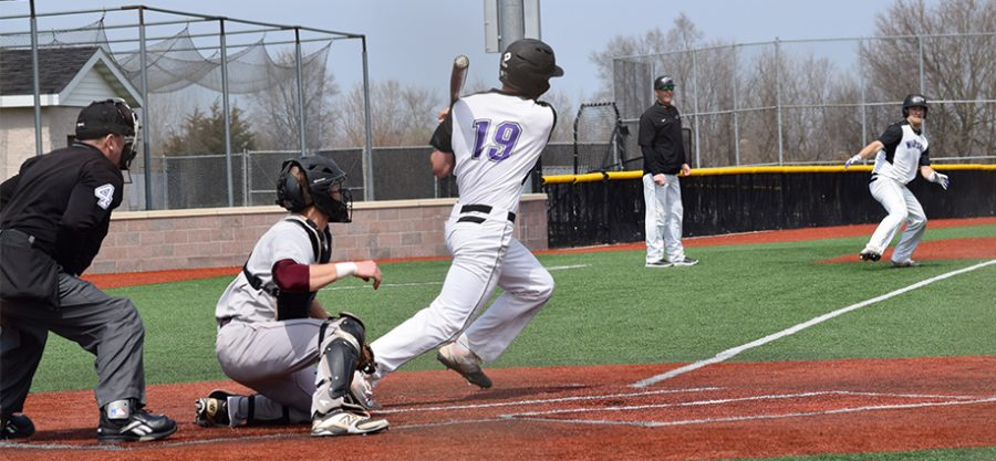 Junior+outfielder+Brett+Krause+begins+running+down+the+first+base+line+after+connecting+on+a+hit+as+freshman+outfielder+Matt+Wary+rounds+third+base+in+an+April+8+doubleheader+vicotry+vs.+UW-La+Crosse.+The+Warhawks+have+now+won+six+straight.+Photo+by+Hannah+Jewell%0A