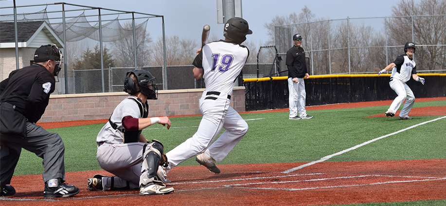 Junior outfielder Brett Krause begins running down the first base line after connecting on a hit as freshman outfielder Matt Wary rounds third base in an April 8 doubleheader vicotry vs. UW-La Crosse. The Warhawks have now won six straight. Photo by Hannah Jewell