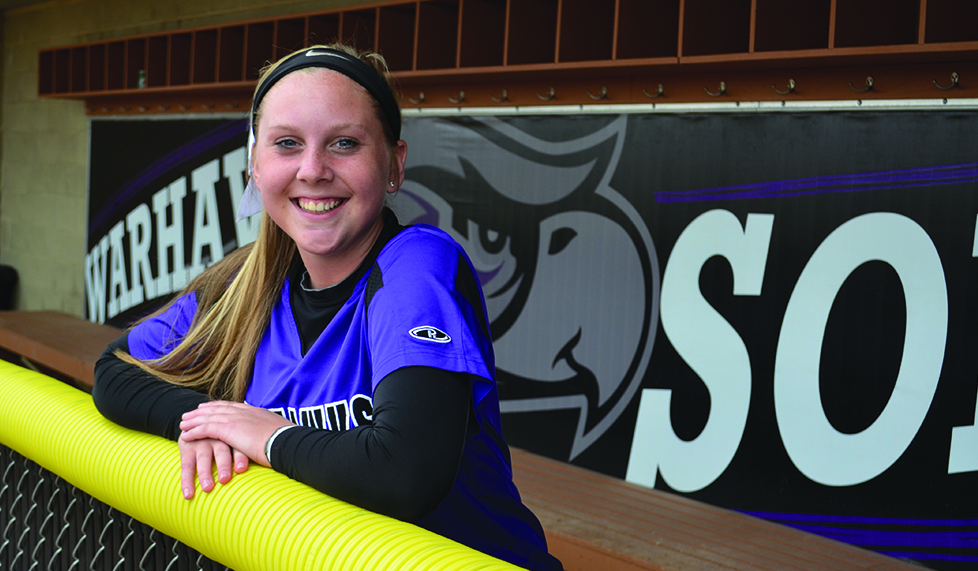 Freshman softball pitcher Bella Matthias is all smiles in the Warhawk dugout and on the mound after being near the WIAC lead in every pitching category. Photo by Sierra High