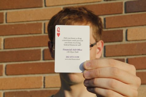 Photo by Sean Kirkby: A former University of Wisconsin-Whitewater student poses with a playing card distributed by the campus warning of the penalties of a drug conviction. The student, who requested anonymity because he is looking for a job, sold drugs to another student on campus who was a confidential informant.