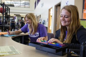 Seniors Glynis Albue and Christine Panella work the front desk at the Williams Center weight room.