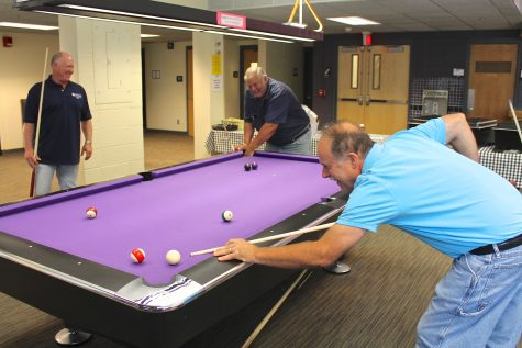 The billiards room in Warhawk Alley in the University Center was filled with custodians enjoying a break from work for a few hours before being served lunch.
