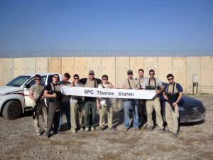 "Slaten poses with his unit holding a banner sent to him from an elementary school that ""sponsored"" him on his deployment."