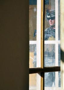 Slaten in uniform through a building window.