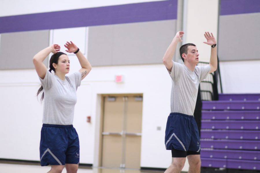 Brienna Herdrich and Justin Nemoir perform jumping jacks during physical training.