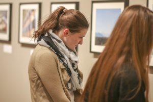 Junior Mary Wentzel examines one of the 47 photos on March 4 in Roberta's Art Gallery in the University Center.