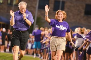 "UW-Whitewater Chancellor Beverly Kopper and interim provost John Stone run through Perkins Stadium before students. Incoming freshman found themselves being swept up into their welcome activities after their arrival on campus on Sunday, August 30. Club U Dub Dub got students interacting with their peers and made them a part of the ""Warhawk family"" by participating in the R U Purple rally, running through Perkins Stadium and painting Warhawk Drive purple. They finished off the night by attending Club 1868. Photo by Aaron Gottschalk."