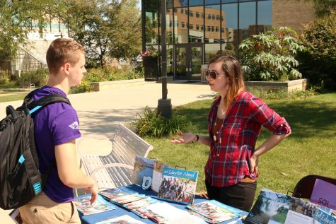 Freshman Zach Galvin talks to an exhibitor about pursuing an education abroad. The Global Experience featured 55 exhibitors along the Wyman Mall between Hyland Hall and the University Center. Photo by Zach Ewoldt.