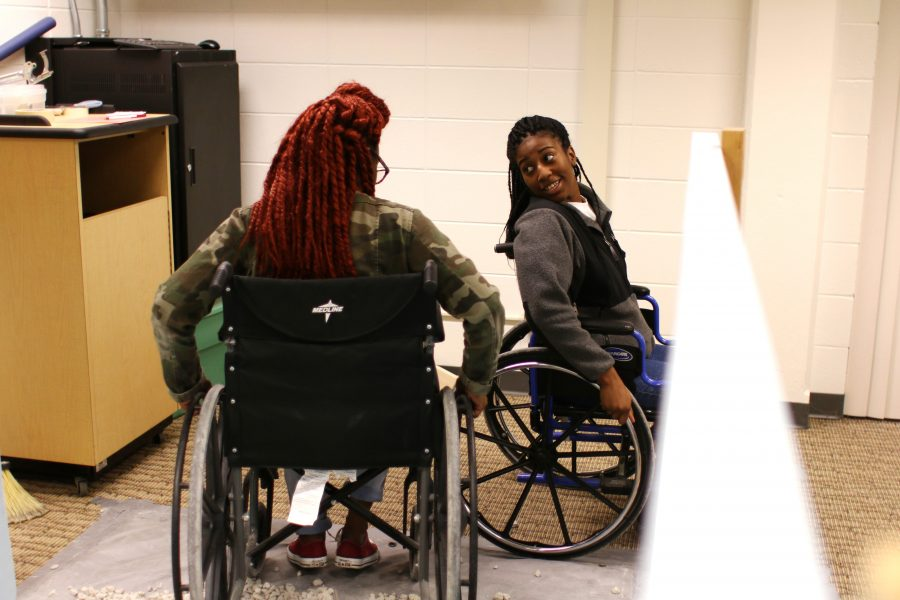 Sophomore Alice Gilliam speaks with another group member as they attempt to roll over gravel and wooden boards with wheelchairs at Boxes and Walls on Oct. 12. Photo by Kimberly Wethal.