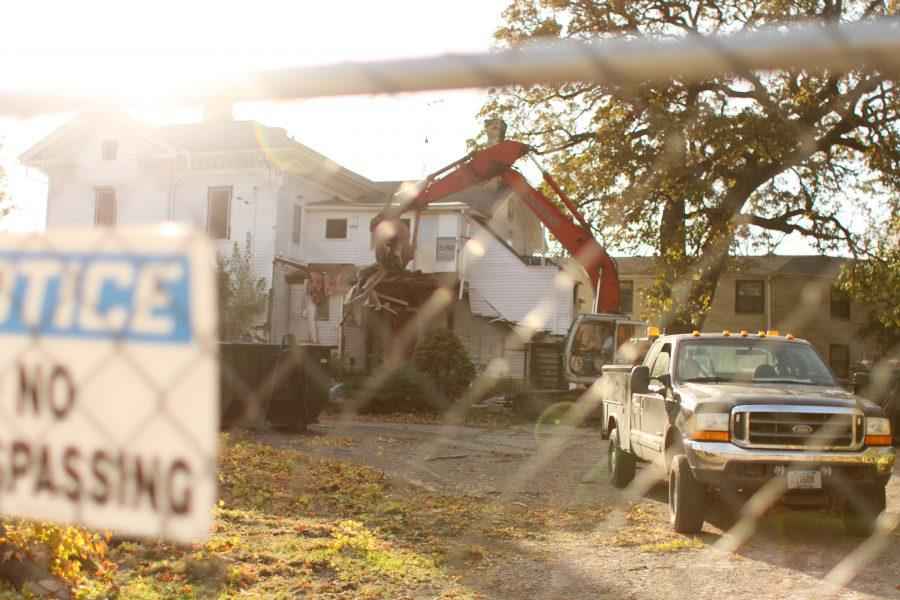 A construction crew member works to take down the former Olsen Funeral Home on Oct. 19, one day after two trees that inspired a student-made petition were cut down. A bur oak still stands behind the house. Once fully demolished, Campus Edge Apartments will be built on the property in its place. Photo Kimberly Wethal