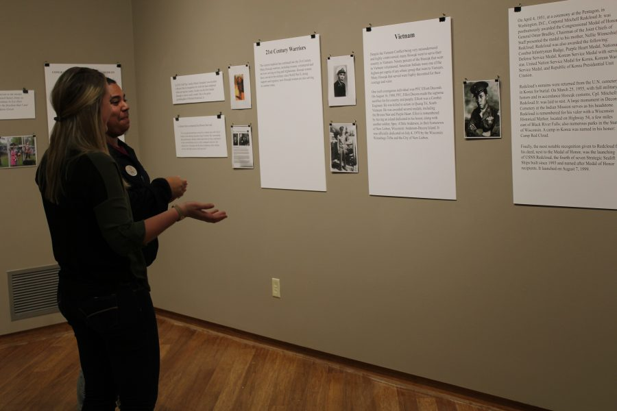 """Senior Quade Rodriguez and sophomore Jordyn Schmidt discuss artwork featured in """"Road of the Warrior: Life of the Ho-Chunk Military Service."""" The exhibit is open from Nov. 9 to 20."""