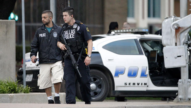 Dallas law enforcement patrols walk down the street a block from the police headquarters. Five members of law enforcement were killed at a Black Lives Matter protest following the deaths of two black men earlier that week. Photo courtesy of the Associated Press.