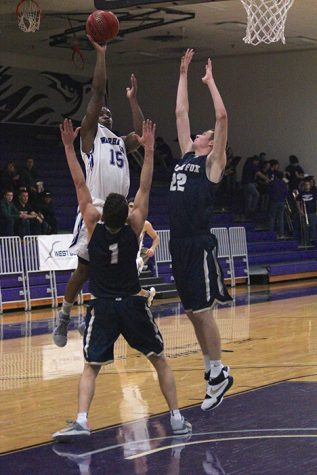 Junior guard Chris Jones shoots over defenders in a home game earlier this year.