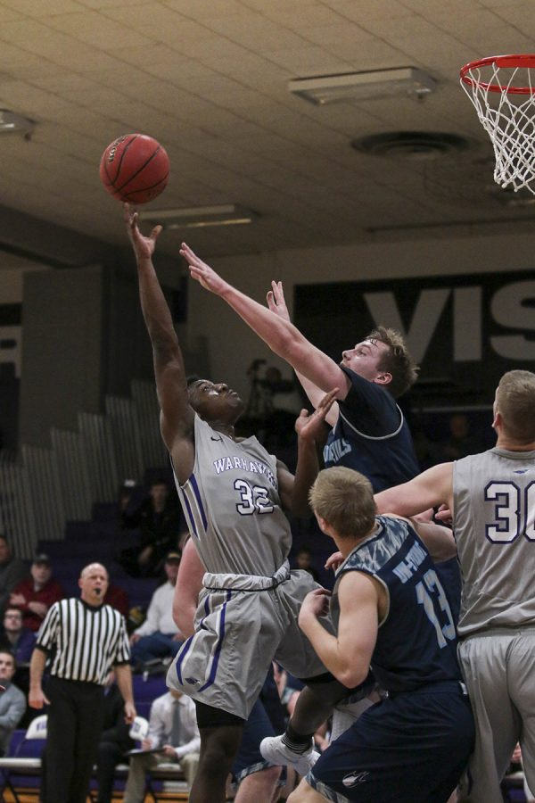 Sophomore guard Maurquis Turner puts up a shot against a  UW-Stout defender. Turner had eight points in the UW-W victory. Photo by Kimberly Wethal