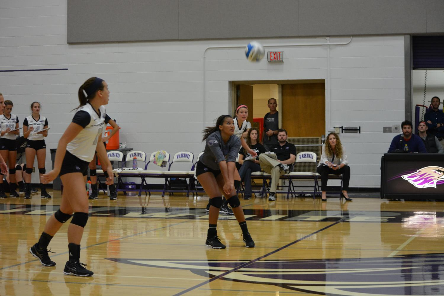 A Warhawks women's volleyball player positions to bump the ball back over the net during a home game.