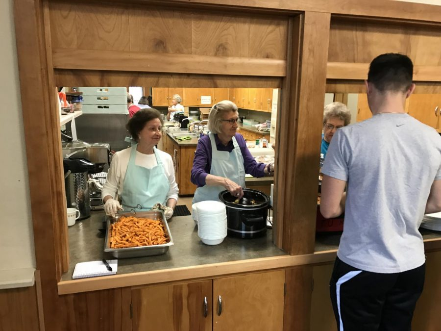 olunteers for First Methodist Church serve hot food to students during a free lunch event. The church has been dishing out hot meals to students and community members for nearly 20 years.