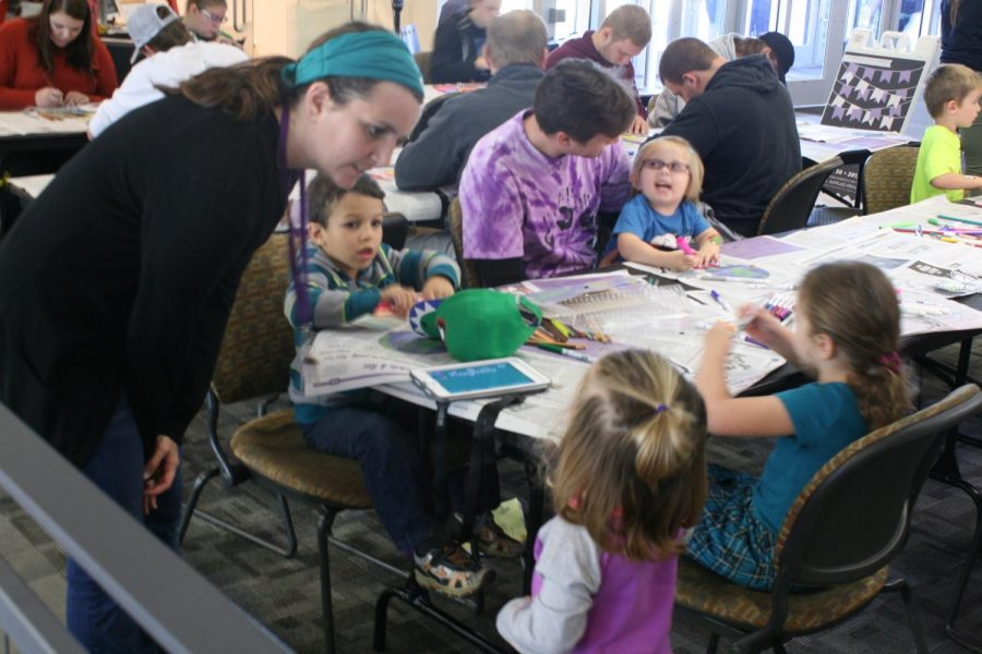 Jenna Kenny, lead 4-K teacher at the Children's Center pre-school program, instructs a group of her students on how to create colorful art in the shape of butterflies Monday at a Divsersity Week event.