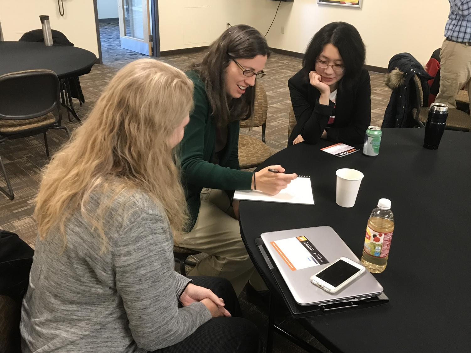 Professors Yao Fu and Karla Saeger (left and far right) discuss their thoughts with librarian Diana Schull (center) after the GooseChase seminar