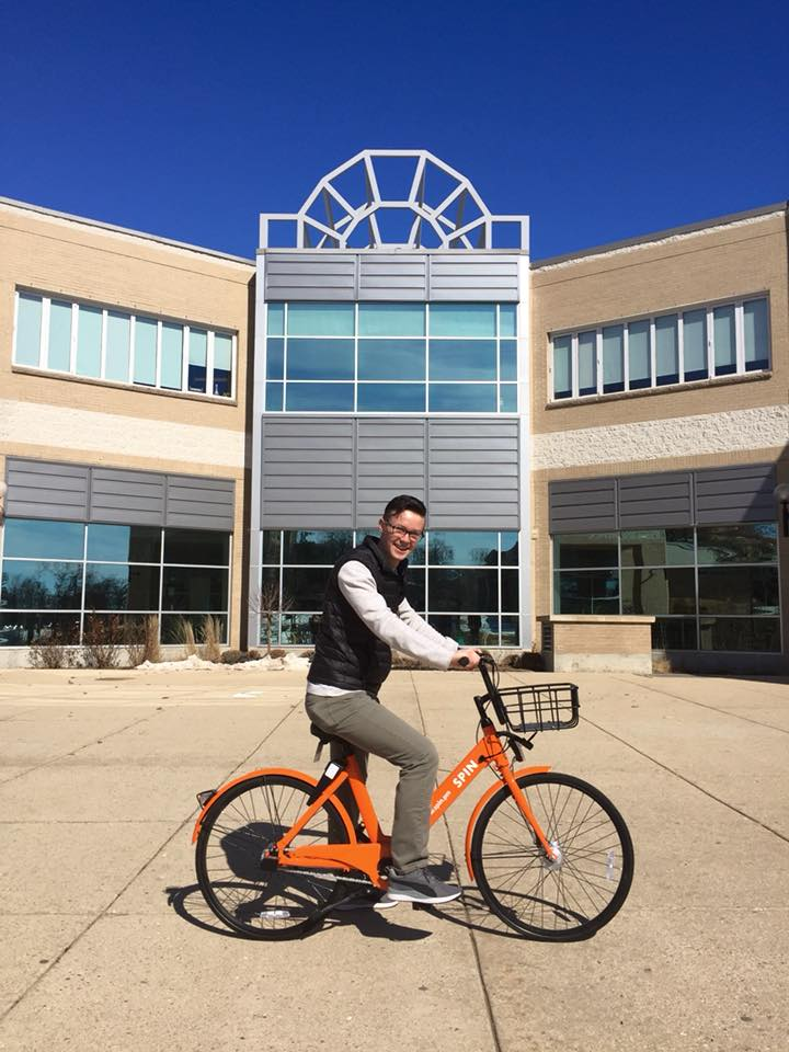 Whitewater Student Government President Tom Kind sits on a Spin ride-share bicycle
