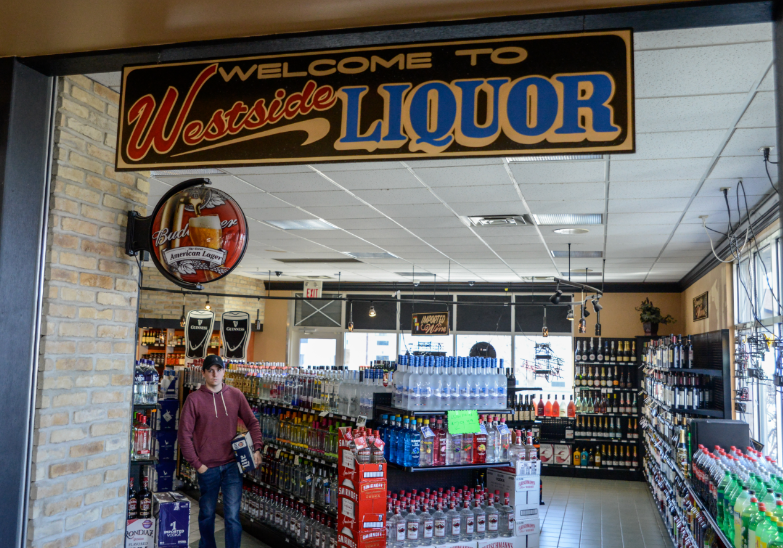 A patron of Westside Liquor heads out the main entrance with their purchase. The liquor store previously was conjoined with Frawley Oil Co., but is now connected to Casey's General Store after the gas station's ownership exchanged hands.