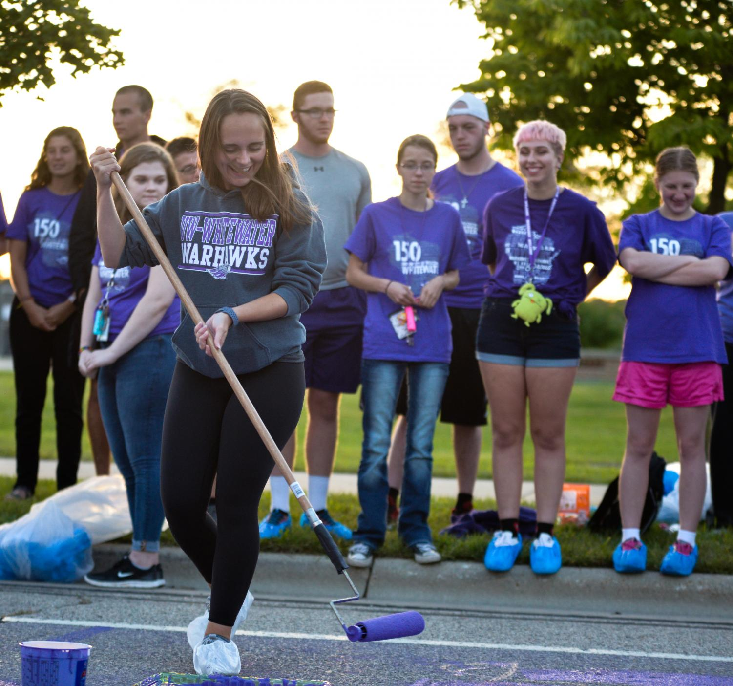 Senior Ally Erck demonstrates how to use a paint roller to freshmen who took part in the tradition of painting Warhawk Drive  purple.
