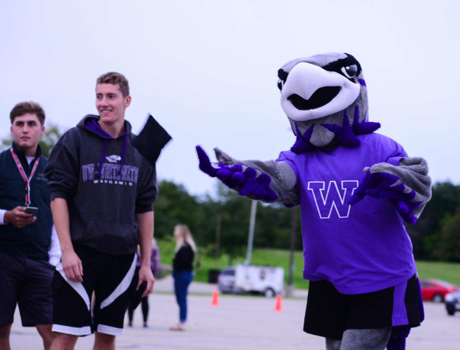 Willie the Warhawk plays a bag toss game with students and community members at his Birthday Bash.