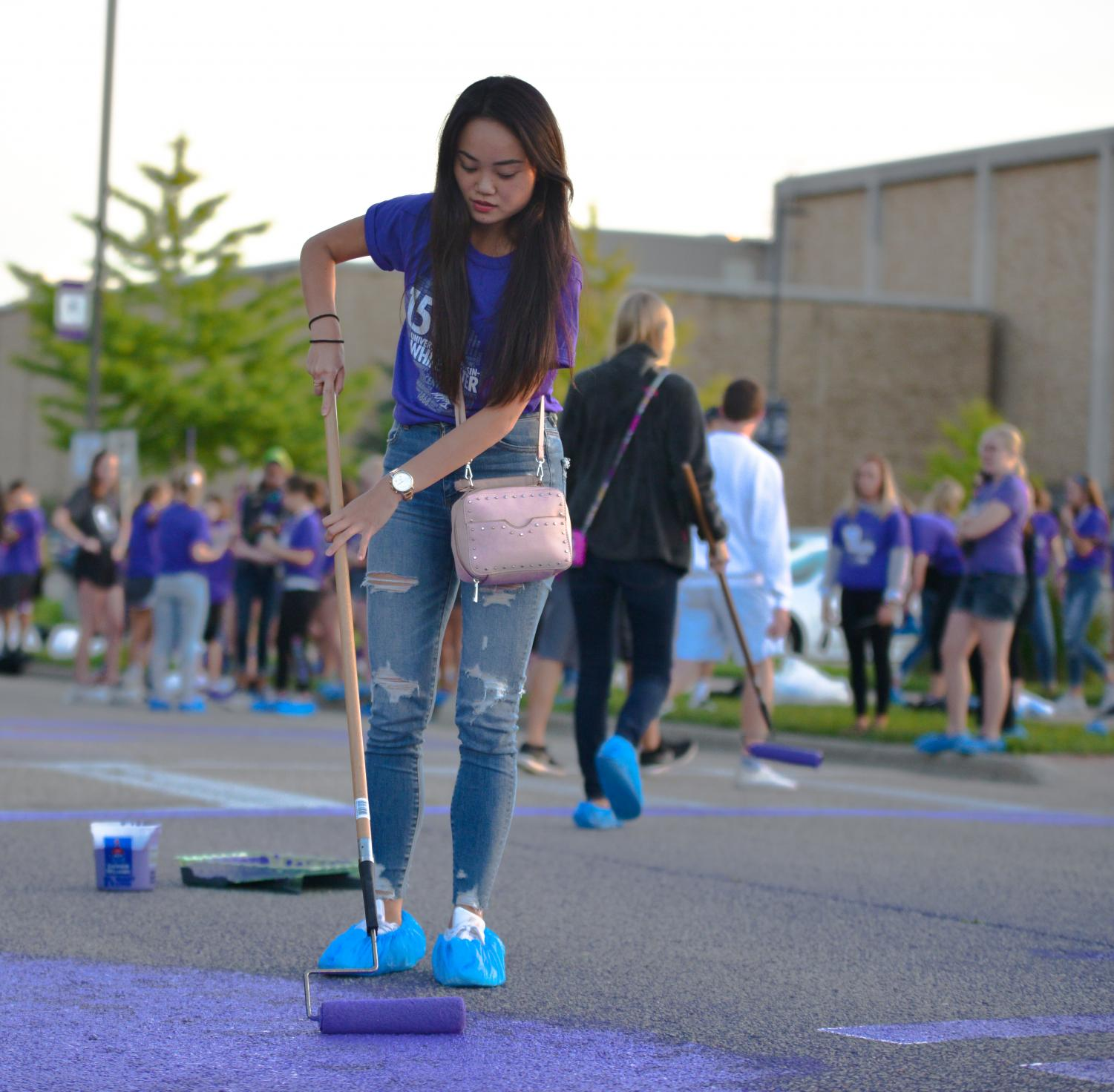 Freshman Rina Tsumuraya applies a fresh coat of purple to Warhawk Drive as a part of the fall orientation process.