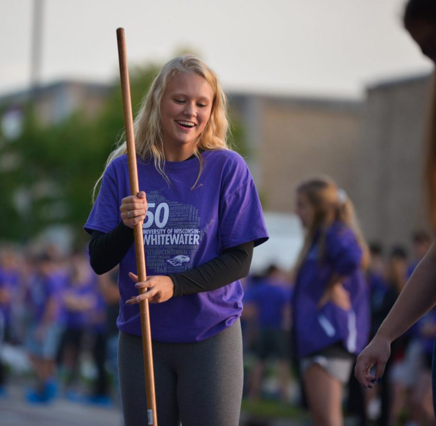 Freshman, Sadie Driscoll paints the pavement purple during 'Warhawk Welcome'