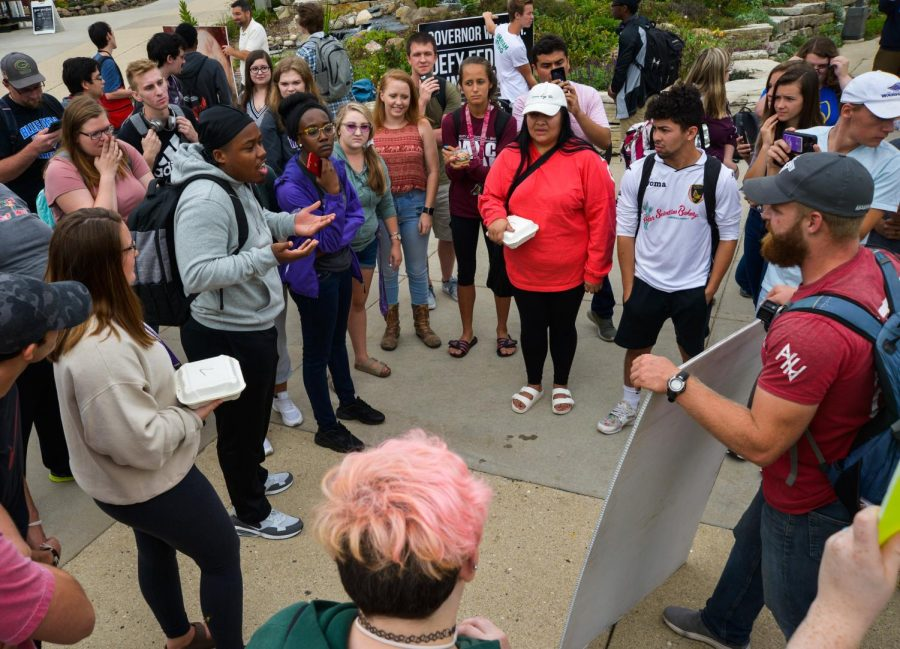 Students debate with an activist from the Abolish Abortion Wisconsin group. The activists came to campus Sept. 19, and some students expressed opposition to the posters on display.
