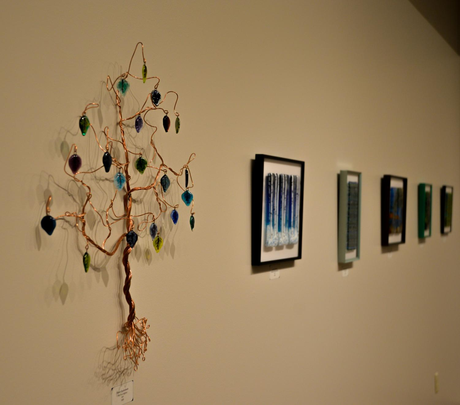 The current exhibit at Roberta's Art Gallery features works by artist Kristin Quackenbush, who  utilizes different colors of broken glass to create visual depth in her pieces.