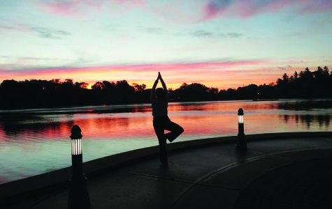 A woman practices and watches the sun rise over Cravath Lake during the morning yoga class.