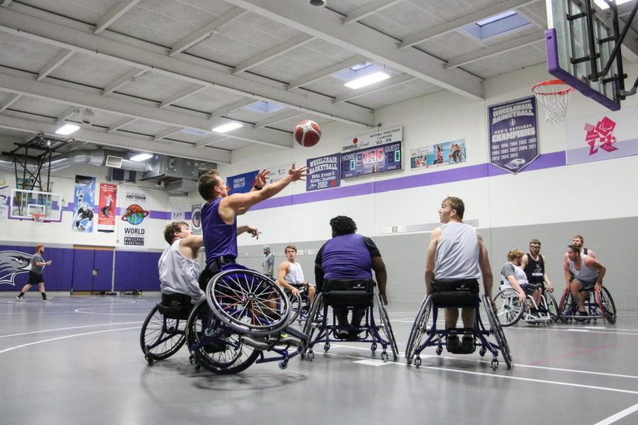 Drew Selz takes a shot during basketball practice as his teammates jockey for position on the rebound.