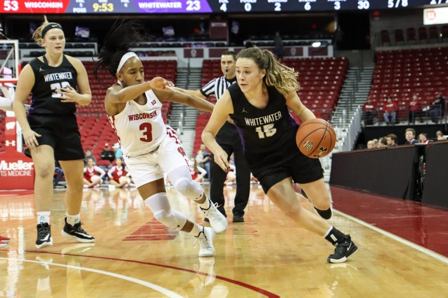 UW-W's Veronica Kieres (15) dribbles past UW-Madison's Suzanne Gilreath on her way to the basket. The Warhawks struggled offensively at the Kohl Center on Oct. 30, but found their rhythm in the second half.