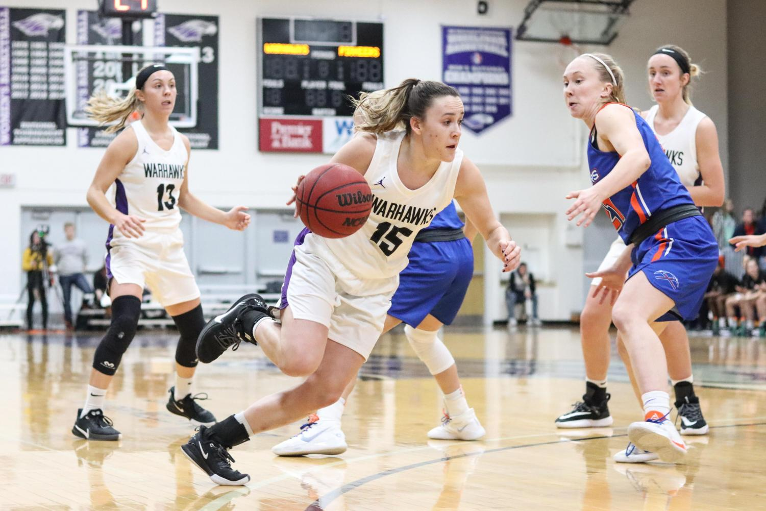 Sophomore Veronica Kieres (15) drives to the hoop off a screen by senior Becky Raeder (13) in the game against Platteville.
