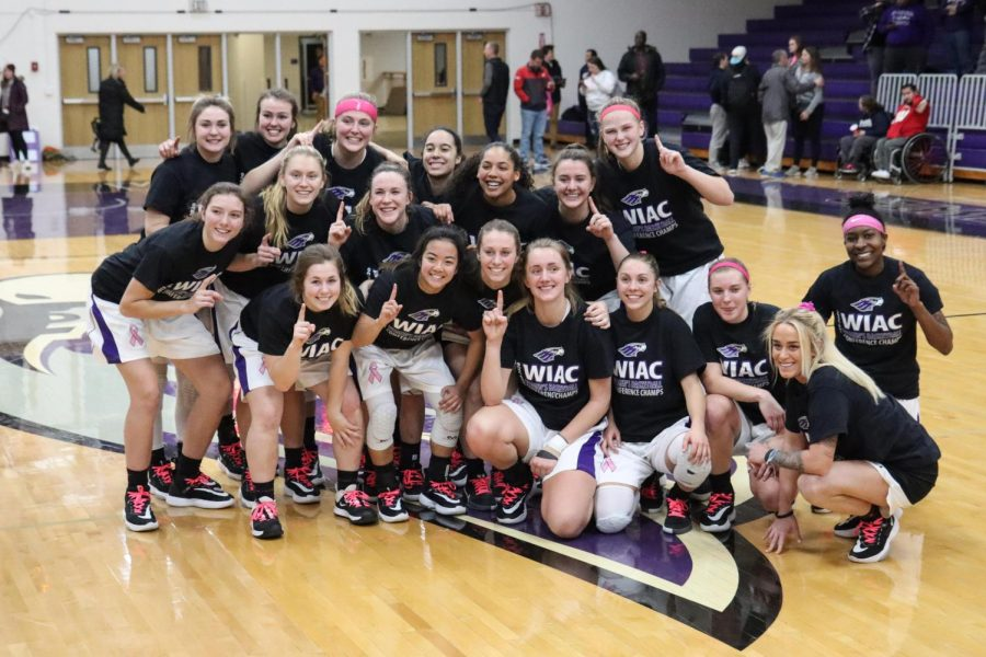 The women's basketball team celebrates winning their ninth regular season conference championship after their win over Oshkosh.