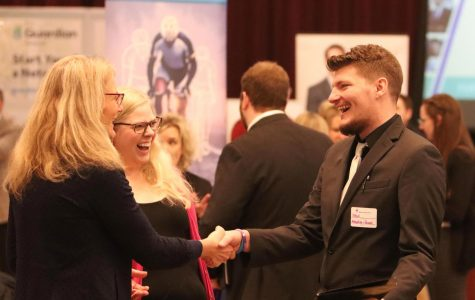 Zach Rogney shakes hands with potential employer, Jan Froelich.