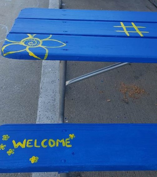 Volunteers paint picnic tables for a new outdoor eating area in downtown Whitewater open through Oct. 31.