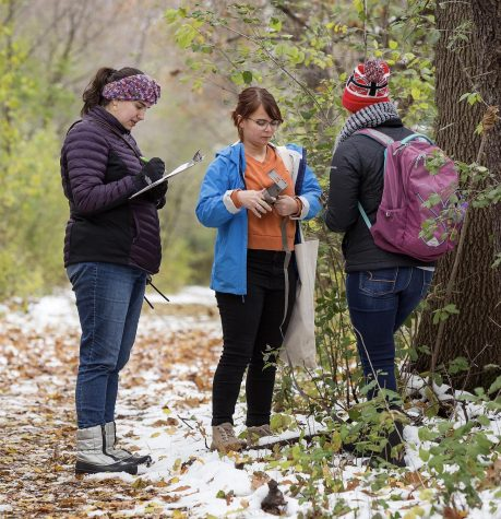 Assistant Professor Andrea Romero, left, writes down data dictated by Regina Rose, facing camera, who is an environmental sciences student from Roscoe, Illinois, and Noel Schmitz, a biology major from Sparta, Wisconsin. Two UW-Whitewater students and their professor, contributed wildlife images to the Smithsonian Snapshot USA project, and collected trail cameras on the campus Nature Preserve on Friday, Nov. 1 2019, the final day of the project.