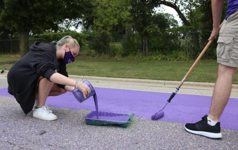 University of Wisconsin-Whitewater student and Hawk Squad member Maddie Neuser (left) adds additional purple paint to a painting tray while Freshman Ryan Waln (right) continues to paint Warhawk Drive nearby.