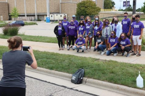 Purple Pit Crew member Katherine Reddeman takes a group photo of Peer Mentor Katie Sorensen and new students who are part of the Live and Learn, learning community, during Warhawk Welcome.