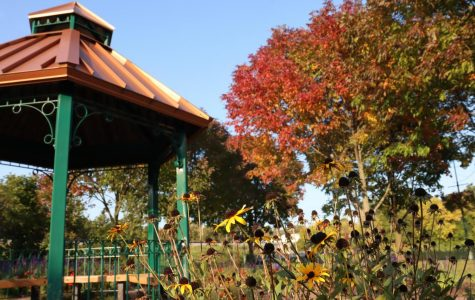 The Gazebo at Cravath Lakefront is surrounded by flowers and a few trees with colorful fall leaves.
