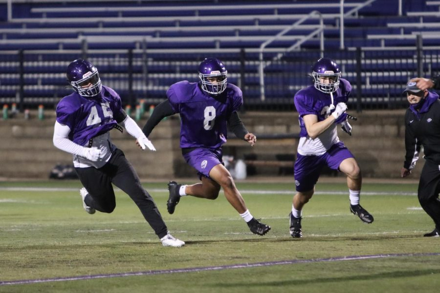 Ryan Liszka, Tyler Precia and Egon Hein run side-by-side in a practice drill during the cool early morning hours Oct. 23 at Perkins Stadium