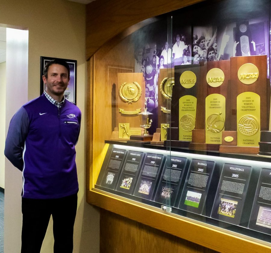 Standing next to some of the woman's championship trophies, Ryan Callahan, the Interim Director of Intercollegiate Athletics, celebrates 50 years of WIAC Woman's sports!