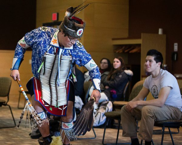Mino-Giizhik DeBungie performs a hunting dance watched by students including UW-Whitewater criminology major Cody Wing, who is president of the Native American Cultural Awareness Association. Debungie is a member of the Red Cliff Band of Lake Superior Chippewa and Wing is a member of the Bad River Band of Lake Superior Chippewa. Six members of the Red Cliff Band of Lake Superior Chippewa from Bayfield County in northern Wisconsin visited UW-Whitewater to talk with students about native culture and perform traditional dances, drumming and singing. Classes in restorative justice, American Indian studies and dance participated through the afternoon on Wednesday, March 6, 2019. (UW-Whitewater photo/Craig Schreiner)