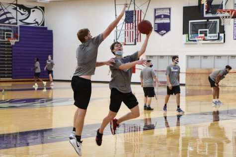 UW-Whitewater men's basketball freshman JT Hoytink (right) goes for a layup while contested on defense by freshman teammate Caleb Flaten-Moore (left) during the team