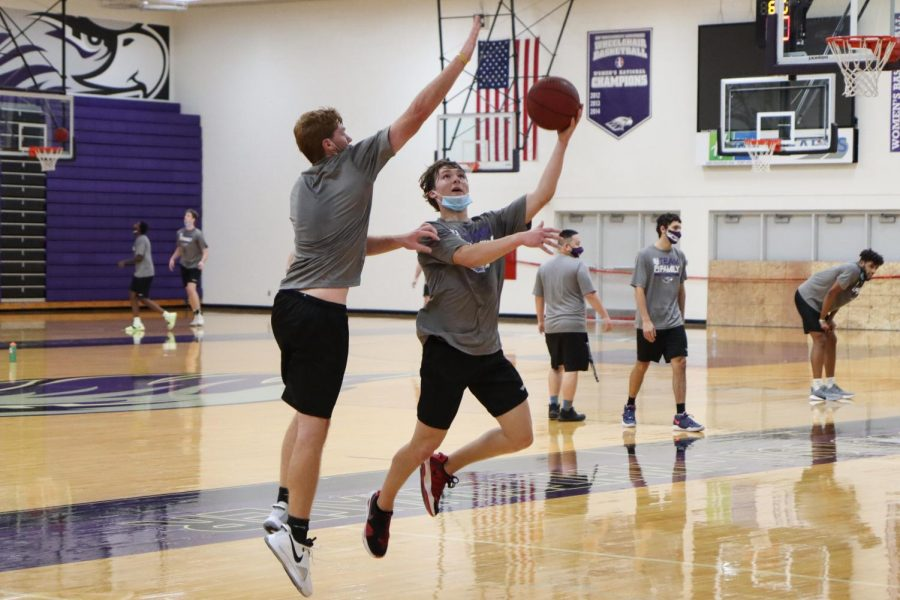 UW-Whitewater men's basketball freshman JT Hoytink (right) goes for a layup while contested on defense by freshman teammate Caleb Flaten-Moore (left) during the team's practice on Friday Oct. 23.