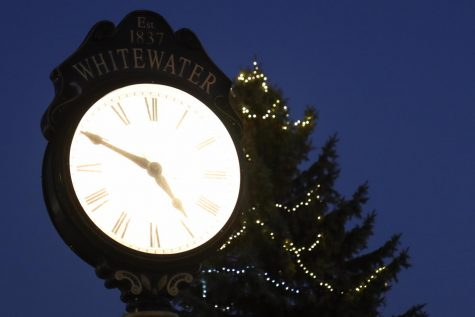 Holiday lights wrapped around a tree shine brightly behind a street clock, along West Main Street in downtown Whitewater.
